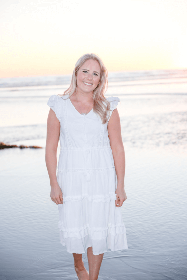 Laura Cragun in a white dress on the beach smiling