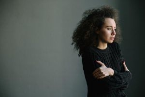 Curly haired woman in a black sweater hugging herself for comfort